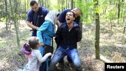 Венгрия полициясы Сербиямен шекарада сириялық босқынды ұстап жатыр. 28 тамыз 2015 жыл. (Көрнекі сурет.)