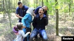 Венгерские полицейские задерживают мигрантов из Сирии на границе с Сербией. 28 августа 2015 года.