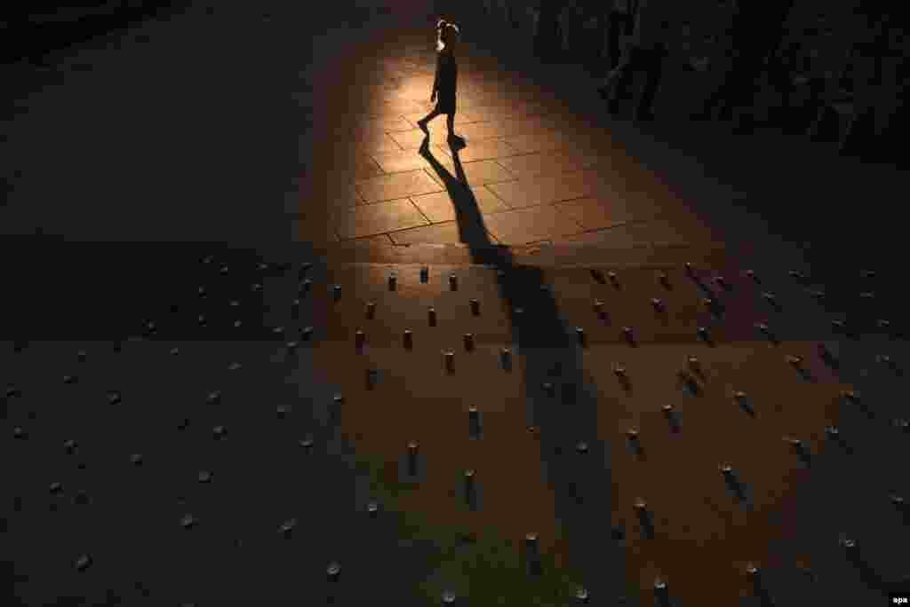 Një vajzë shqiptare ecën përsakj qirinjve të ndezur në sheshin në Prishtinë, për të nderuar viktimat nga të shtënat afër një qendre tregtare në Munih. Tre kosovarë kanë vdekur në këtë incident.