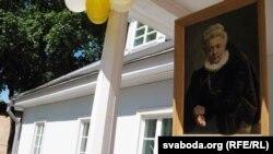 партрэт Элізы Ажэшкі на фоне яе дому
