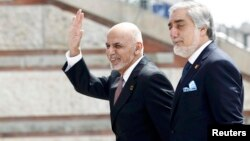 Afghan President Ashraf Ghani (right) with the country's Chief Executive Officer Abdullah Abdullah as they arrive for the NATO summit in Warsaw in July 2016.