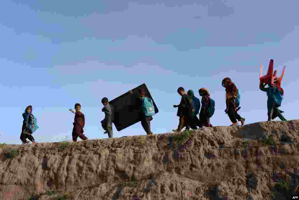 Afghan schoolchildren carry their blackboard and a chair as they walk home after classes at an open-air school outside a brick factory on the outskirts of Jalalabad. (AFP/​Noorullah Shirzada)
