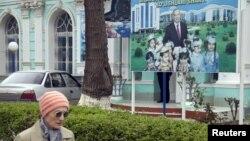 Женщина проходит рядом с билбордом с изображением кандидата в президенты и действующего президента Узбекистана Ислама Каримова, установленным рядом с избирательным участком. Ташкент, 29 марта 2015 года.