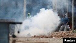 Pamje e protestuesve në Kashmir duke gjuajtur gurë mndaj policëve që kishin hedhur gaz lotsjellës