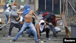 Үкіметке наразылар полицияға тас лақтырып жатыр. Каракас, 22 ақпан 2014 жыл.