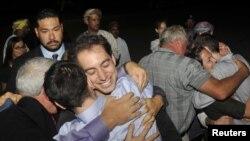 Джош Фэттал (слева) и Шейн Бауэр при встрече с членами своих семей в столице Омана Маскате