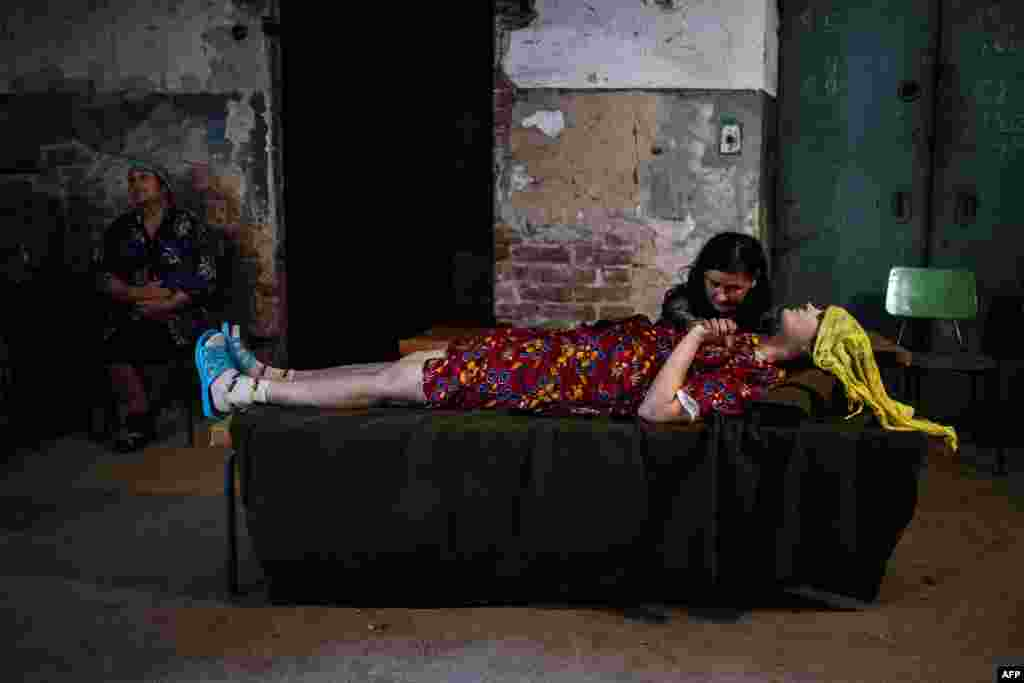A woman holds the hand of her sick friend in the basement of a hospital after shelling in Donetsk. (AFP/Dimitar Dilkoff)