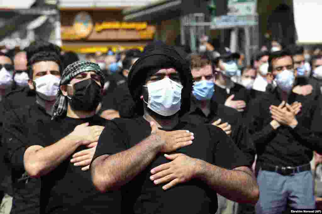 Believers in face masks beat their chests during the annual ceremony commemorating Ashura on August 30.