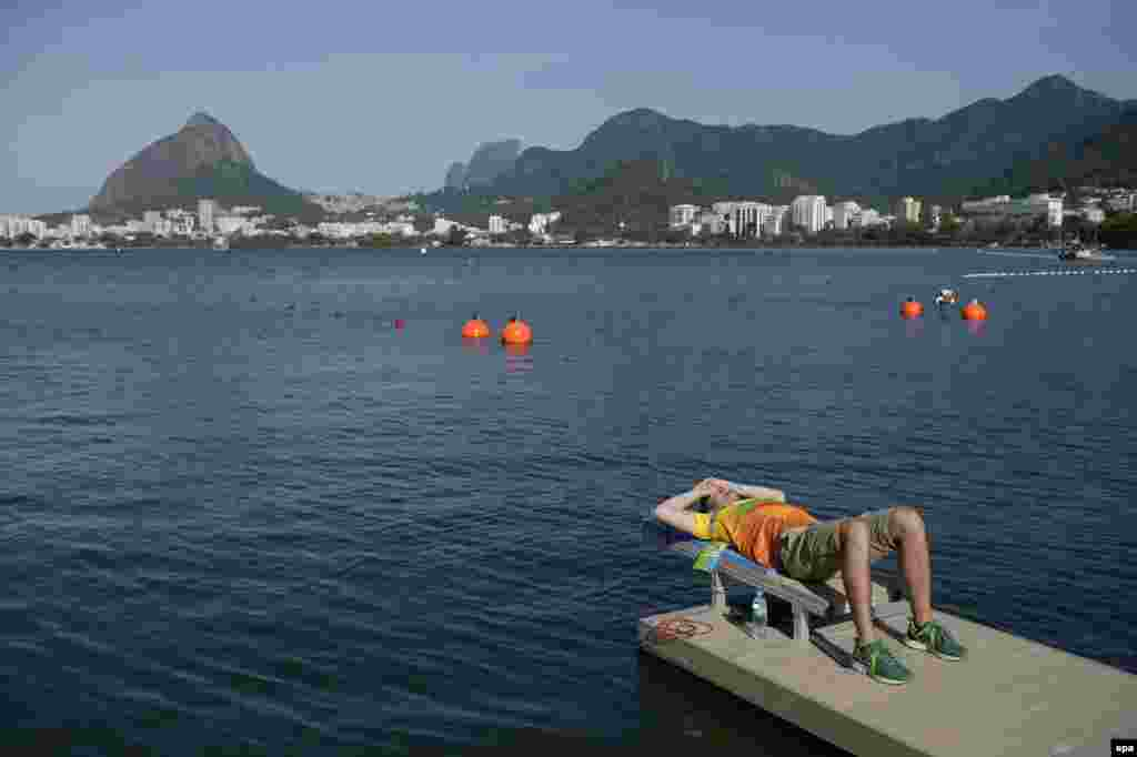 A worker at the Lagoa venue waits out a weather delay for rowing events caused by strong winds.