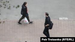 Прохожие на улице в Алматы во время карантина. 15 апреля 2020 года.
