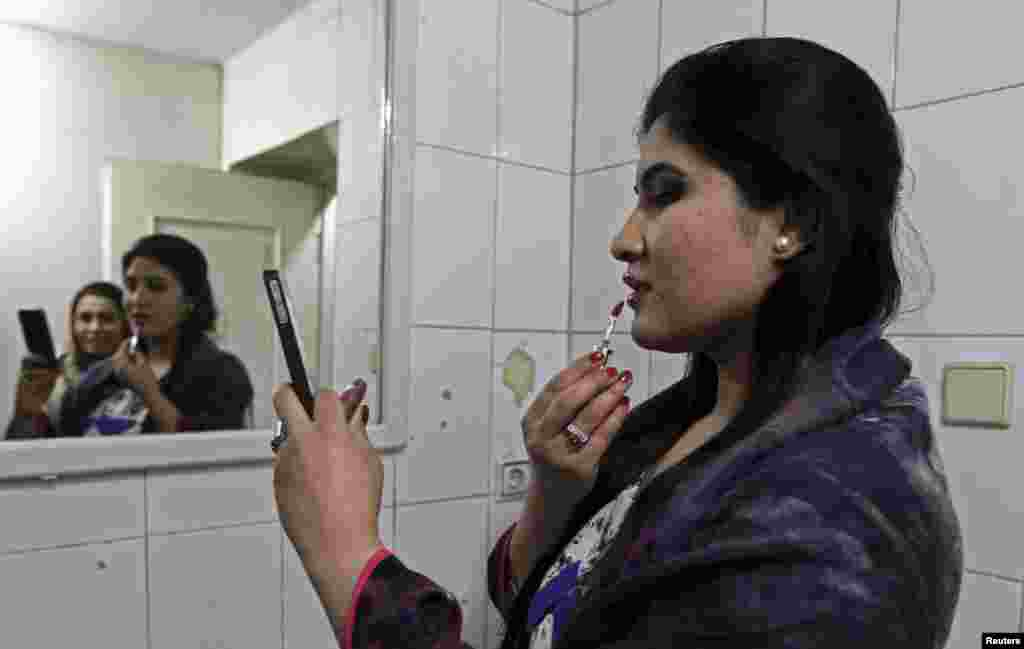 An Afghan model applies makeup before presenting creations designed by Afghan women at a fashion show launched by Young Women for Change in Kabul. (Reuters/Omar Sobhani)