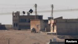 """Черный флаг группировки """"Исламское государство"""" над городом Кобани. 9 октября 2014 года."""