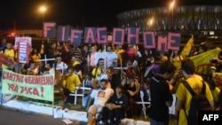 گروهی از معترضان که تا پاسی از شب در خیابانها ماندهاند با شعار «فیفا به خانهات برگرد» در برازیلیا، پایتخت برزیل