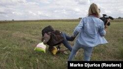 Një migrant më fëmijë rrëzohet për tokë pasi shqelmohet nga kameramanja Petra Laszlo