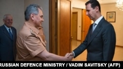 A file photo of Russian Defense Minister Sergei Shoigu (left) shaking hands with Syrian President Bashar al-Assad during a meeting in Damascus in 2016.