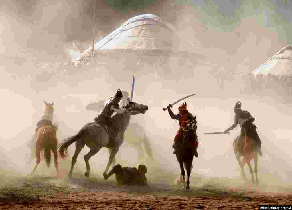 Horsemen fight through clouds of dust during a simulated battle as part of the kickoff.