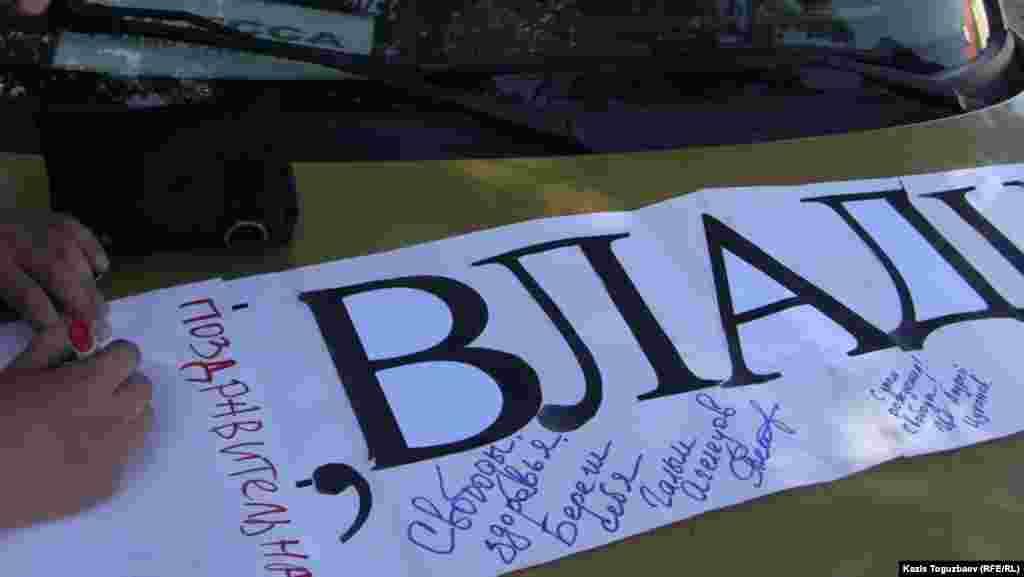 Участники акции написали свои пожелания на транспаранте с поздравлением заключенного оппозиционного политика Владимира Козлова.