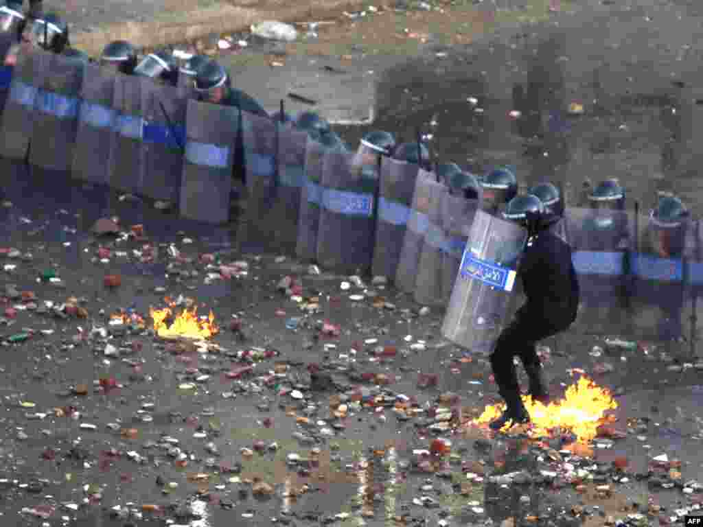 A police officer catches fire from a fire bomb thrown at police battling demonstrators in Suez January 27.