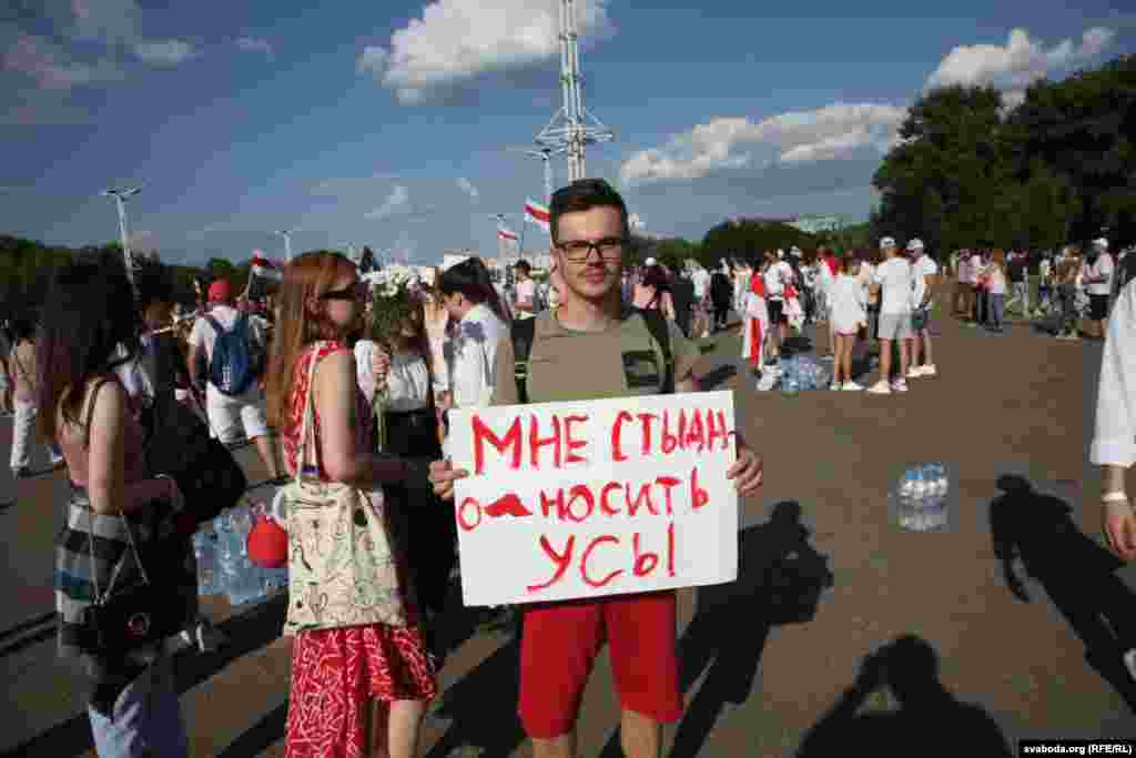 "A man holds a sign that says, ""I'm ashamed to wear a mustache,"" referring to the same facial hair worn by Lukashenka."