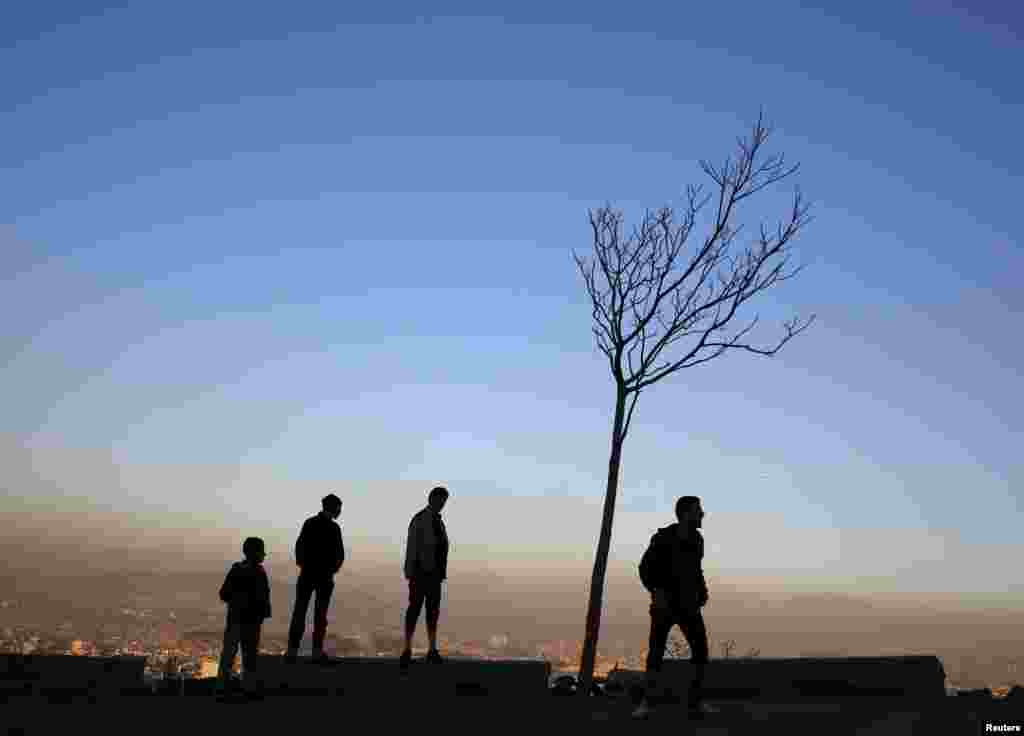 People stand next to a tree overlooking Kabul city on February 1. (Reuters/Ahmad Masood)