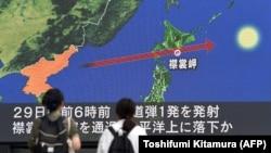 Прохожие на улице разглядывают на большом экране точный маршрут северокорейской ракеты, пролетевшей над Хоккайдо. Токио, 29 августа