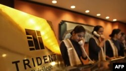 Receptionists answer telephones at the front desk of the reopened Trident Hotel in Mumbai.