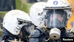 Belgian riot police are covered by hay and eggs thrown by demonstrators as farmers from all over Europe took part in a demonstration outside an EU farm ministers emergency meeting at EU Council headquarters in Brussels on September 7.