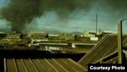 Остров Кунашир, пара загорает на крыше сарая в Южно-Курильске. Черный дым на заднем плане – горящие автомобильные покрышки на местной свалке мусора