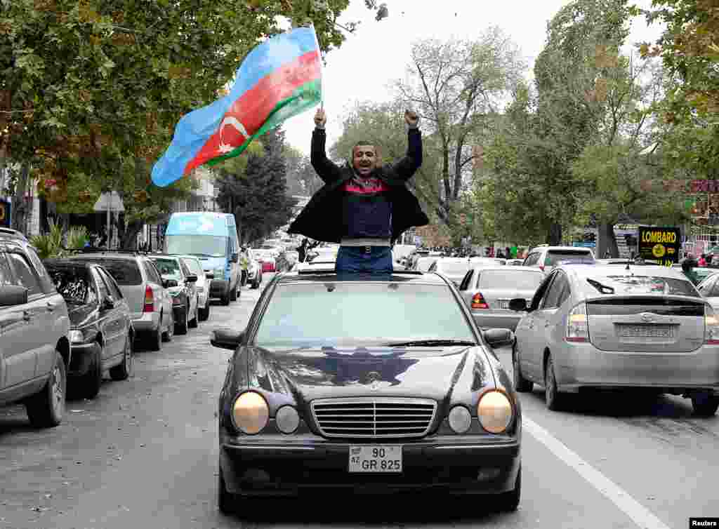 A man in Baku joins crowds celebrating in the Azerbaijani capital after President Ilham Aliyev claimed on November 8 that his forces had captured the city of Shushi/Susa.
