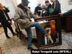 Участник акции протеста в Бишкеке, ворвавшийся в Белый дом, пинает портрет президента страны Сооронбая Жээнбекова, 6 октября 2020 года.