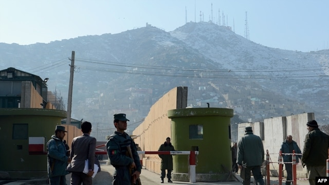 Afghan policemen stand guard at the entrance to police headquarters on December 24 in Kabul where a female police officer shot dead a foreign civilian adviser.