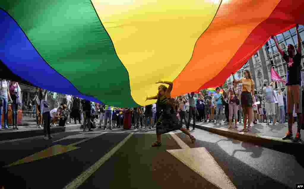 A woman dances under a huge rainbow flag during the good-humored festivities.