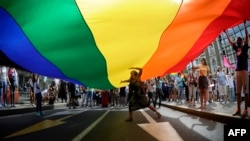 A woman dances under a huge rainbow flag during a gay pride parade in Belgrade on September 18.