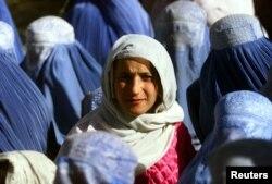 Молодая афганская женщина впервые показывает свое лицо на публике после пяти лет действия законов талибов, ожидая в центре раздачи еды в центре Кабула 14 ноября 2001 года