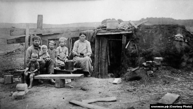 Семья спецпереселенцев рядом с землянкой