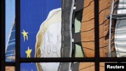 Отражение баннера с евро в окнах фасада штаб-квартиры Еврокомиссии в Брюсселе