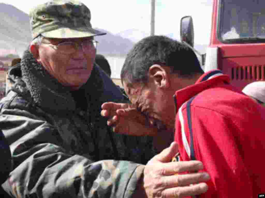 A man is comforted by rescue personnel. - Caption : A Kyrgyz man cries at the site of a major earthquake in Nura on October 6, 2008. Rescuers raced to reach a remote village in Kyrgyzstan on Monday after a strong earthquake killed at least 72 people in a mountainous area near the border with China, officials said. The quake late Sunday, which measured magnitude 6.6 according to the US Geological Survey (USGS), razed the village of Nura in the isolated Alaisky district, high in the Tian Shan mountain range.