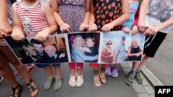 بستگان خانوادهای شش نفره که در حمله نیس کشته شدند، عکسهای قربانیان را در دست دارند