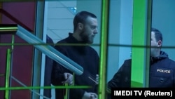 Jack Shepherd is escorted inside a police station in Tbilisi on January 23.