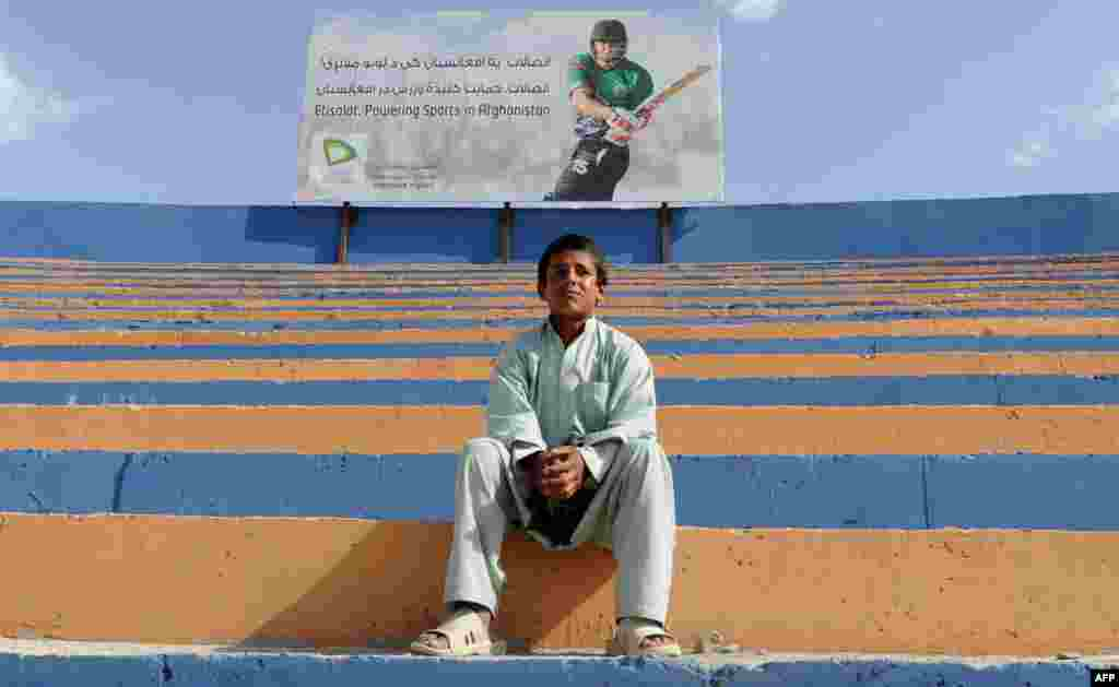 An Afghan youth watches a regional cricket tournament in Kabul on May 29. (AFP/Aref Karimi)