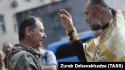 Священик благословляє російського полковника Ігоря Гіркіна (Стрєлкова), на той час одного з ватажків угруповання «ДНР», що визнане в Україні терористичним. Окупований Донецьк, 10 липня 2014 року