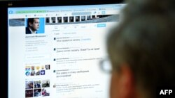 A man looks at the computer screen in Moscow with a Twitter page showing Russian Prime Minister Dmitry Medvedev.