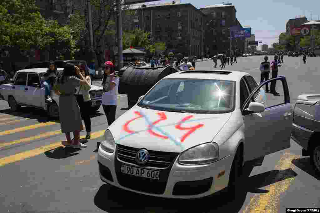"The name of Armenia's ruling Republican Party (HHK) crossed out on the hood of a protester's car in Yerevan. Opposition leader Nikol Pashinian said the HHK's parliamentary faction had ""destroyed itself irreversibly"" and announced ""war against its own people"" by refusing to support his candidacy for prime minister."