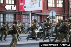 Armed security forces move to intervene against protesters in Minsk on August 10.