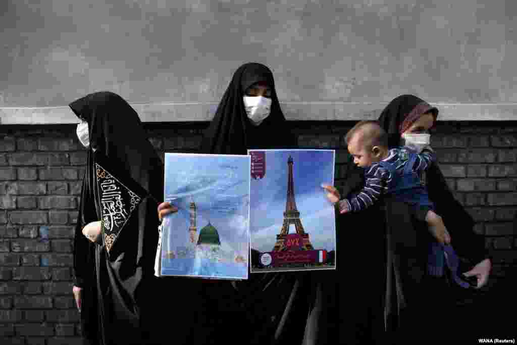 A protester holding pictures of France's Eiffel Tower and the Prophet's Mosque in Medina, Saudi Arabia, takes part in a protest to condemn the French magazine Charlie Hebdo for republishing cartoons of the Prophet Muhammad in front of the French Embassy in Tehran on September 9. (WANA via Reuters/Majid Asgaripour)