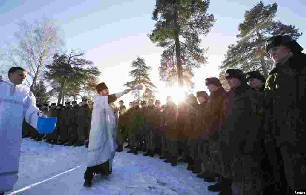 Belarusian security forces take part in a service near an Orthodox church at a military base in Minsk.