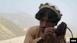FILE: A picture made available on 20 June 2014 shows a local tribesman listening to news on a radio after Pakistani military launched an offensive in North Waziristan.