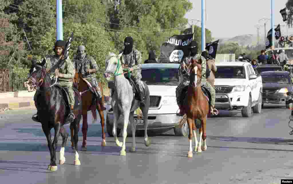 Militant Islamist fighters ride horses as they take part in a military parade along the streets of Syria's northern Raqqa Province on June 30. (Reuters)
