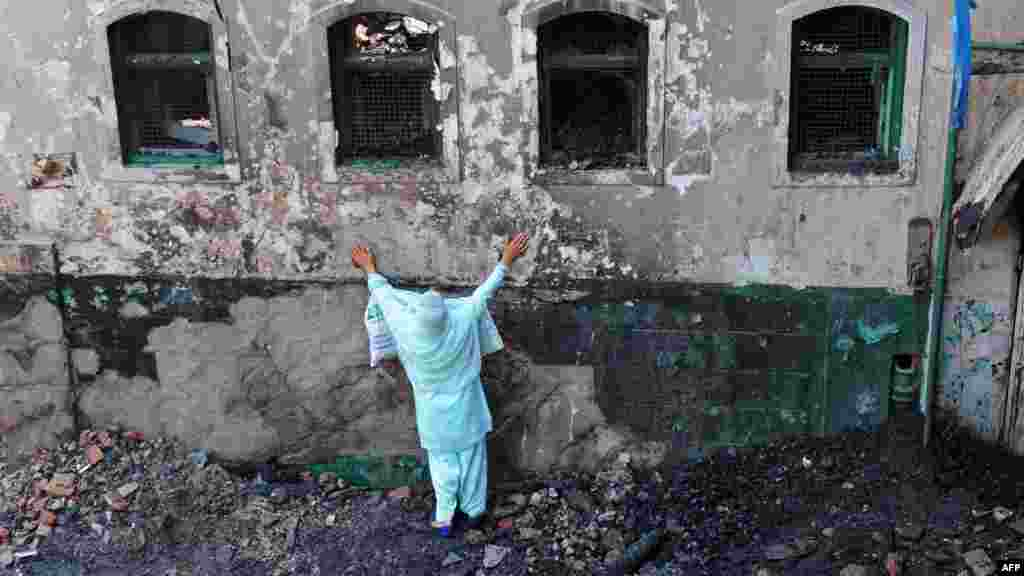 A Muslim woman grieves as unseen fire personnel and volunteers clear debris from the charred remains of the 200-year-old shrine of Sheikh Abdul Qadir Jeelani in downtown Srinagar, in the Indian state of Jammu and Kashmir. (AFP/Rouf Bhat)