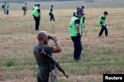 Бойовик угруповання «ДНР» спостерігає за роботою експертів на місці падіння «Боїнгу»